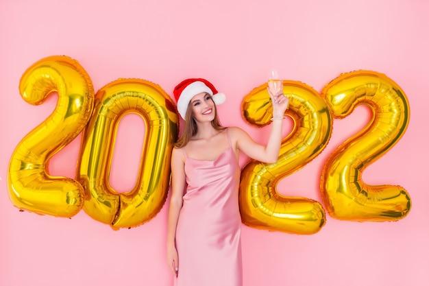 Opgewonden jong santameisje werpt glas champagne gouden nummers luchtballonnen nieuwjaarsconcept op