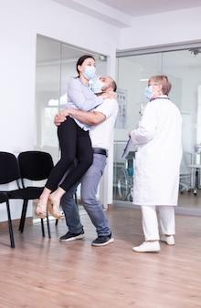 Opgewonden jong stel na goed ontvangen van arts met gezichtsmasker in wachtruimte van ziekenhuis