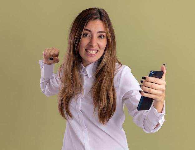 Opgewonden jong, vrij blank meisje houdt vuist en houdt telefoon geïsoleerd op olijfgroene muur met kopieerruimte