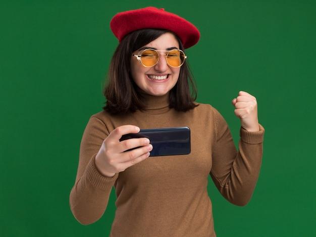 Opgewonden jong, vrij kaukasisch meisje met barethoed in zonnebril houdt vuist en houdt telefoon vast