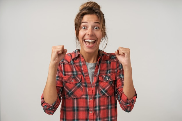 Opgewonden jonge aantrekkelijke brunette vrouw met natuurlijke make-up emotioneel verhogen van haar handen terwijl opgewonden kijken naar de camera, staande op een witte achtergrond