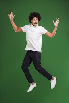 Opgewonden jonge afrikaanse krullende man springen geïsoleerd
