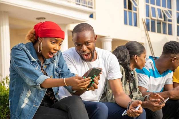 Opgewonden jonge afrikanen voelen zich opgewonden terwijl ze naar een mobiele telefoon kijken en met vrienden zitten