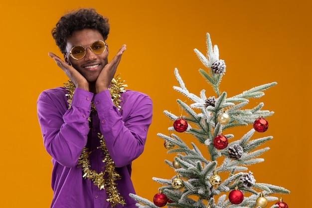 Opgewonden jonge afro-amerikaanse man met bril met klatergoud slinger rond nek staande in de buurt van versierde kerstboom handen houden op gezicht geïsoleerd op oranje muur