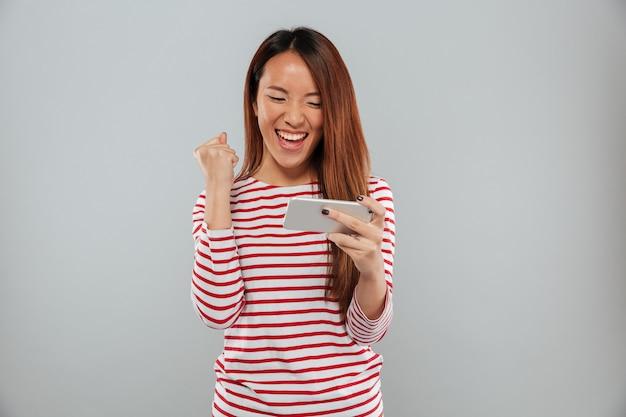 Opgewonden jonge aziatische dame spelen spelletjes via de telefoon