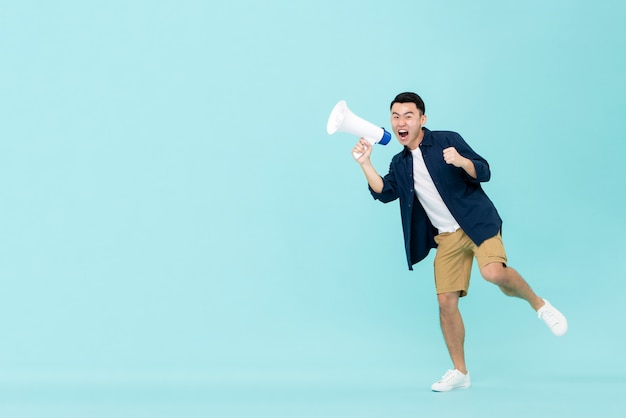 Opgewonden jonge aziatische man met megafoon en schreeuwen