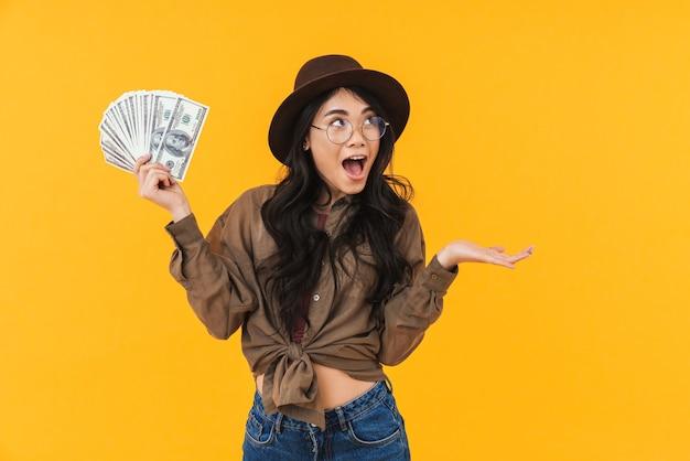 Opgewonden jonge aziatische vrouw die geldbankbiljetten toont terwijl ze geïsoleerd op geel staat