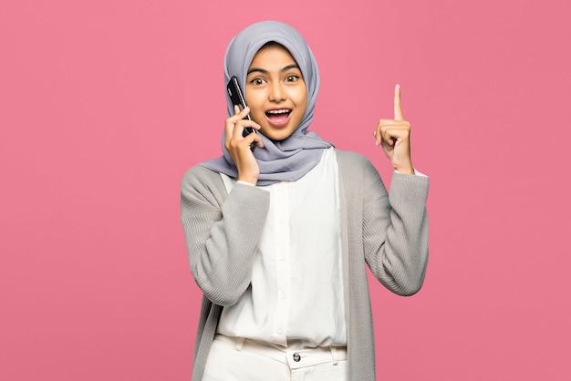 Opgewonden jonge aziatische vrouw die op mobiele telefoon spreekt en een idee heeft en vinger omhoog wijst