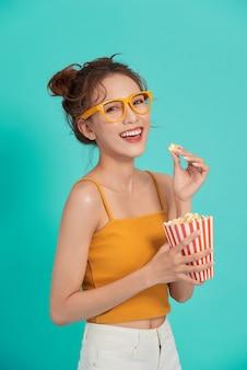 Opgewonden jonge aziatische vrouw die popcorn eet die op blauw wordt geïsoleerd.