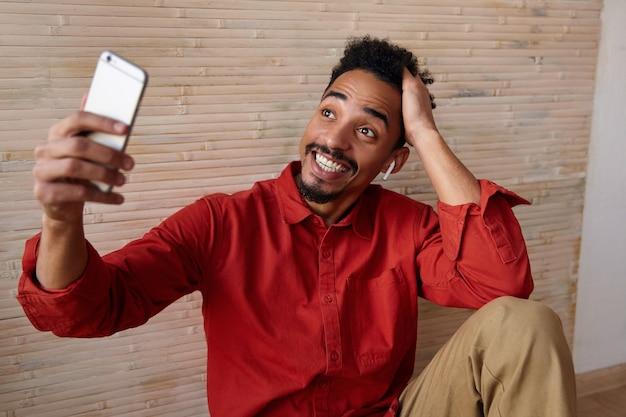 Opgewonden jonge, bebaarde donkere man met baard die de hand omhoog houdt terwijl hij aangenaam telefoneert en breed lacht, poseren op beige interieur