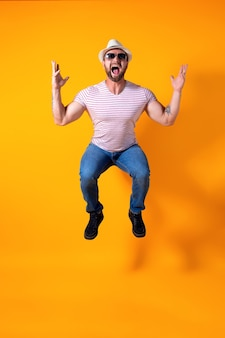 Opgewonden jonge bebaarde fitness sportieve man in hoed en zonnebril springen erg emotioneel geïsoleerd op geel on