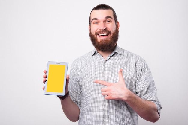 Opgewonden jonge, bebaarde man houdt een tablet vast en wijst ernaar en glimlacht naar de camera bij een witte muur