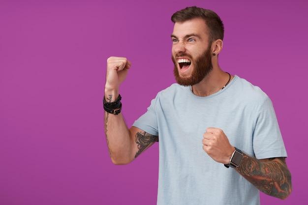 Opgewonden jonge, bebaarde man met tatoeages die een blauw t-shirt dragen terwijl hij op paars staat, opzij kijkt met brede mond open en vuist omhoog houdt