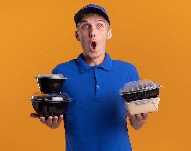 Opgewonden jonge blonde bezorger houdt voedselcontainers en pakket geïsoleerd op oranje muur met kopieerruimte