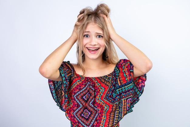 Opgewonden jonge blonde slavische meid die handen op haar hoofd legt en