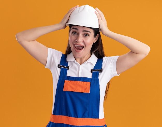 Opgewonden jonge bouwer vrouw in uniform greep hoofd geïsoleerd op oranje muur