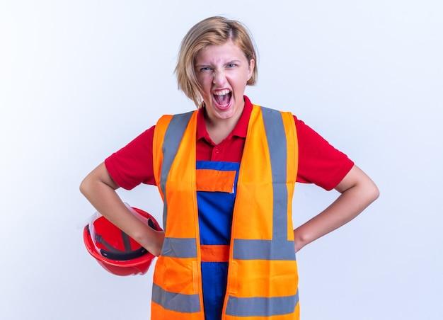 Opgewonden jonge bouwer vrouw in uniform handen op heup geïsoleerd op een witte muur
