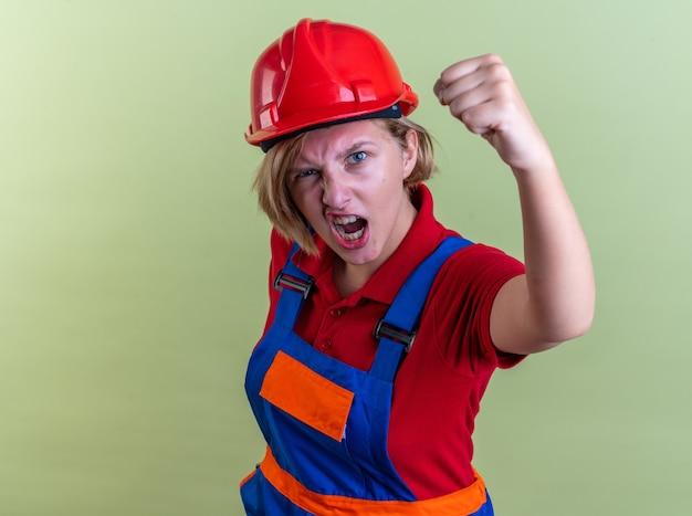 Opgewonden jonge bouwer vrouw in uniform met ja gebaar geïsoleerd op olijfgroene muur