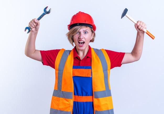 Opgewonden jonge bouwer vrouw in uniform verhogen steeksleutel geïsoleerd op witte achtergrond isolated