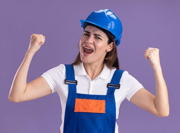 Opgewonden jonge bouwersvrouw in uniform die ja gebaar toont dat op purpere muur wordt geïsoleerd