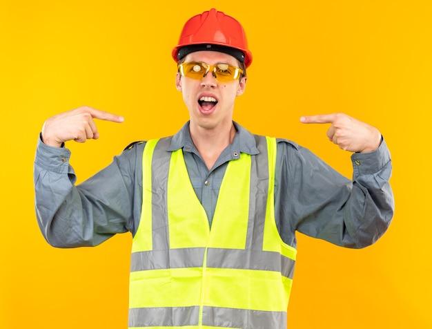 Opgewonden jonge bouwman in uniform met een bril wijst naar zichzelf