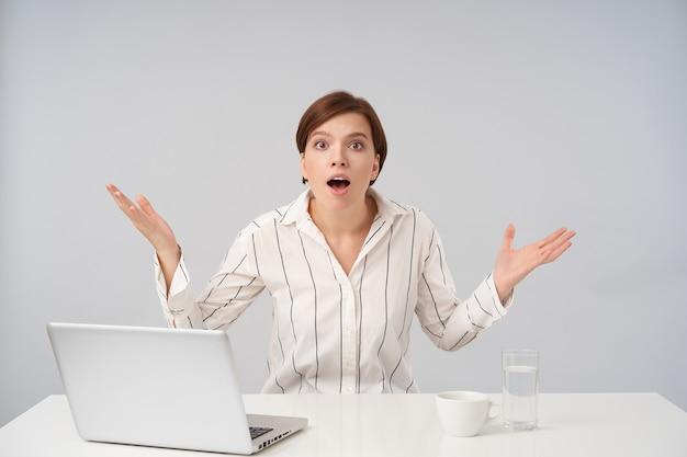 Opgewonden jonge bruinharige vrouw met kort trendy kapsel met grote ogen en mond geopend en opgewonden handpalmen verhogen, geïsoleerd op wit