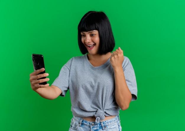 Opgewonden jonge brunette blanke vrouw houdt vuist en kijkt naar telefoon geïsoleerd op groene achtergrond met kopie ruimte