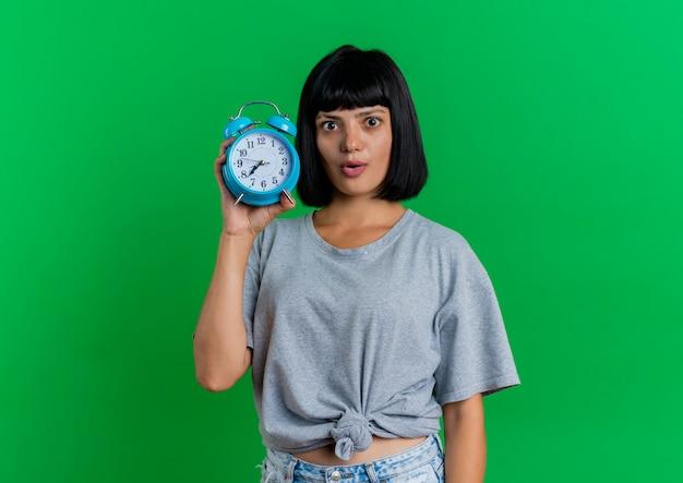 Opgewonden jonge brunette blanke vrouw houdt wekker geïsoleerd op groene achtergrond met kopie ruimte