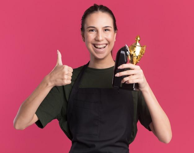 Opgewonden jonge brunette kapper meisje in uniform duimen omhoog en houden tondeuses en winnaar beker geïsoleerd op roze muur met kopie ruimte