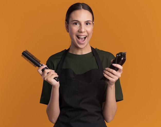 Opgewonden jonge brunette kappersmeisje in uniform houdt tondeuses en kam geïsoleerd op een oranje muur met kopieerruimte