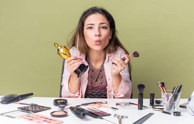 Opgewonden jonge brunette meisje zittend aan tafel met make-up tools met make-up borstel en winnaar cup
