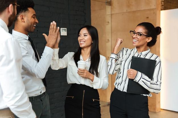 Opgewonden jonge collega's geven een high-five aan elkaar.