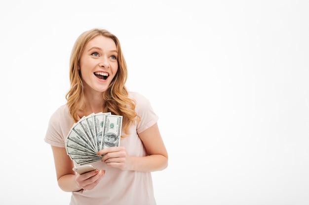Opgewonden jonge dame die geld met behulp van de mobiele telefoon.