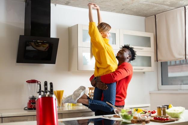 Opgewonden jonge dame glimlachend en handen ophangen terwijl zorgzame liefdevolle vriend haar in zijn armen in de keuken houdt