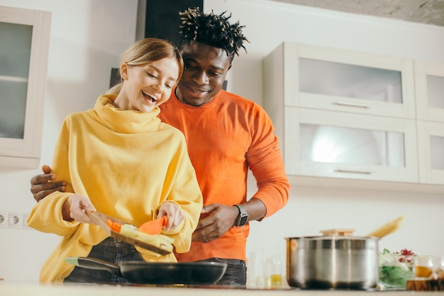 Opgewonden jonge dame groenten op de koekenpan zetten en glimlachen terwijl vrolijke vriendje achter haar rug staan en kijken naar het kookproces