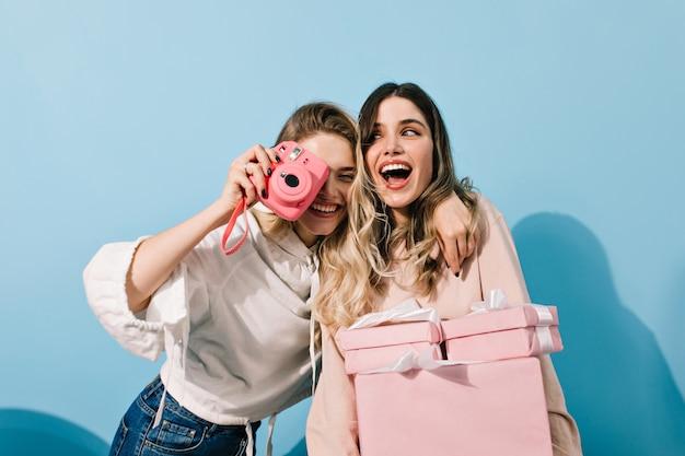 Opgewonden jonge dames die foto's maken op een feestje