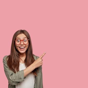 Opgewonden jonge europese vrouw die onder positieve indruk is, naar rechts wijst, iets ongelooflijks ziet, een brede glimlach heeft