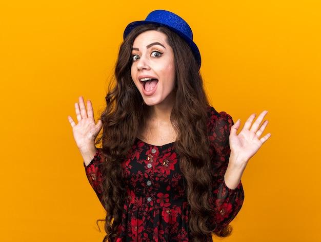 Opgewonden jonge feestvrouw met een feesthoed die naar de voorkant kijkt en lege handen toont die op een oranje muur zijn geïsoleerd