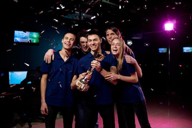 Opgewonden jonge gamers in dezelfde t-shirts poseren met cybersports cup onder vallende confetti in computerclub