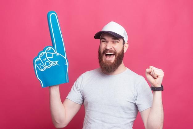 Opgewonden jonge gelukkig man weg wijzen met ventilator schuim handschoen