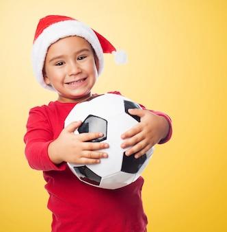 Opgewonden jonge jongen die een omhelzing geeft aan zijn nieuwe bal