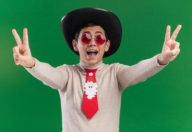Opgewonden jonge kerel die hoed met kerstmisband en bril draagt die vredesgebaar toont dat op groene achtergrond wordt geïsoleerd