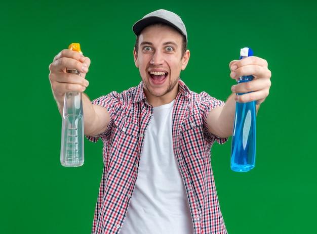 Opgewonden jonge kerel schoner met pet met reinigingsmiddel geïsoleerd op groene muur