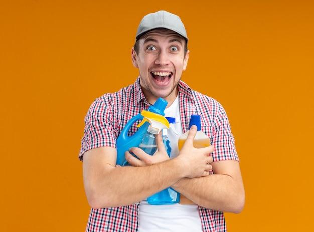 Opgewonden jonge kerel schoner met pet met schoonmaakgereedschap geïsoleerd op een oranje achtergrond