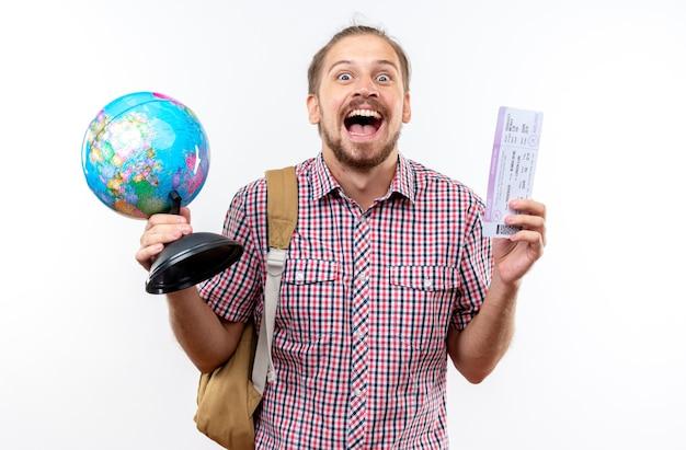 Opgewonden jonge kerel student dragen rugzak met globe met kaartjes geïsoleerd op een witte muur