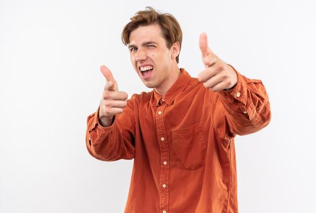 Opgewonden jonge knappe kerel die een rood overhemd draagt dat duimen omhoog laat zien geïsoleerd op een witte muur