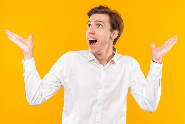 Opgewonden jonge knappe kerel die een wit overhemd draagt dat handen kruist die op oranje muur worden geïsoleerd