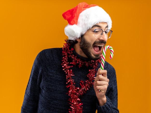 Opgewonden jonge knappe kerel die kerstmishoed met slinger op hals draagt die kerstmissuikergoed houdt dat op oranje achtergrond wordt geïsoleerd