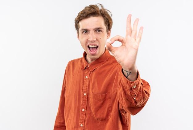 Opgewonden jonge knappe kerel met een rood shirt met een goed gebaar