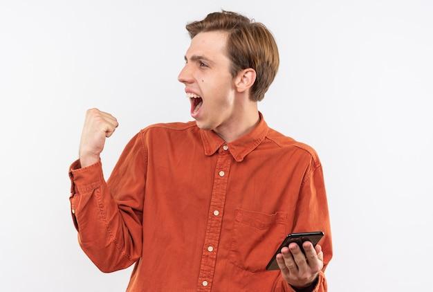 Opgewonden jonge knappe kerel met een rood shirt met een telefoon die een ja-gebaar toont